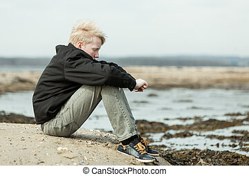 Lonely child with arms around knees outside - Side view on...