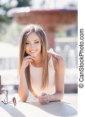 Beautiful girl at a table in a cafe on the background of the...