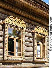 Windows of old log house with carved wooden trim