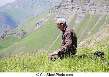 Praying man kneeling - Senior man kneeling while praying in...