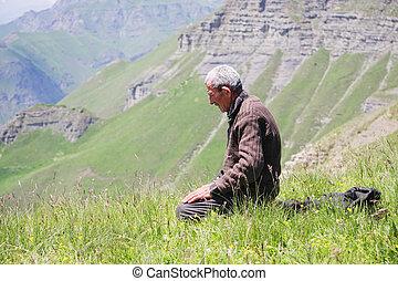 Praying man kneeling - Senior man kneeling while praying in...
