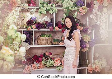 Beautiful asian woman florist in pink dress in flower store...