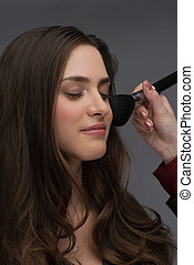 professional makeup artist working - removing excess of...