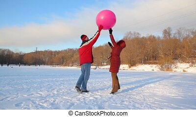 couple plays with air-balloon in snowfield outdoor - happy...