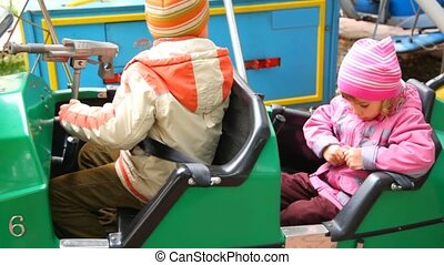 boy and girl sits in dodgem in city park amusement - boy and...