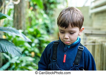 boy sad offended close up portrait on the green trees background