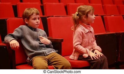 Impressionable girl and boy sits on chair in empty auditorium of circus