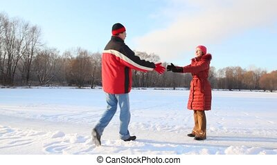 couple having joined hands spins in snowfield - happy young...