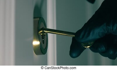 Person wearing black gloves opens locked door with a key....