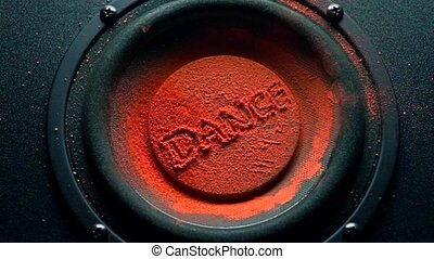 Dance caption on orange powder over trembling speaker. Super slow motion shot