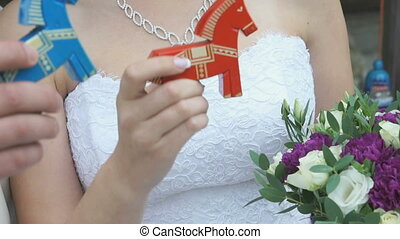 Married couple holding colorful wooden horses toy - Bride...