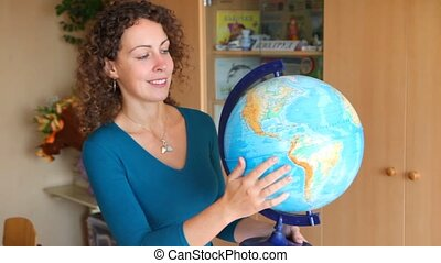woman rotates terrestrial globe in classroom - smiling young...