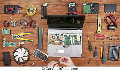 A man checks the details of a laptop with a multimeter. Disassembled computer, a wooden table top view. Touch the contacts and check readings