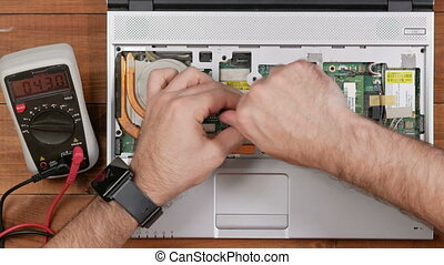 Male engineer assembles the laptop with a screwdriver after...