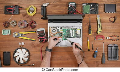 Male engineer solder board laptop at the workplace. Wooden table top view.