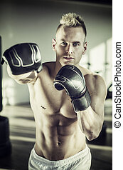 Shirtless young man giving punch with boxing gloves