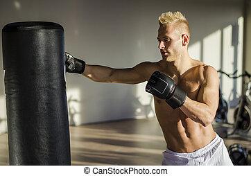 Shirtless young man using punching bag