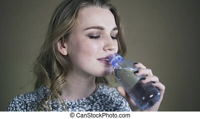 Young woman drinking water. Studio real time shot. - Young...