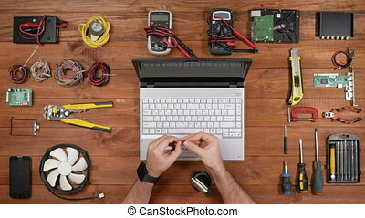 Man repairman connects computer Heat-wire with a gas torch. Wooden table top view