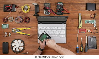 Male technician to disassemble the hard disk to be checked. Wooden table top view