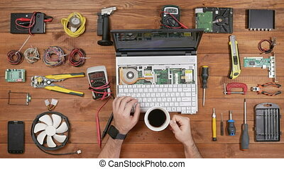 Male engineer computer repair works with disassembled...