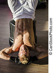 Young man working out in gym, exercising abs