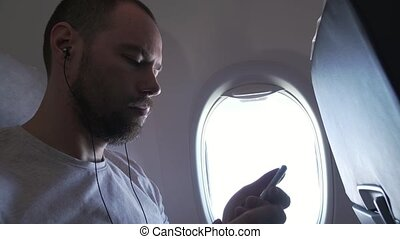 Man sitting near the window of flying airplane and listening to music on headphones with your smartphone.