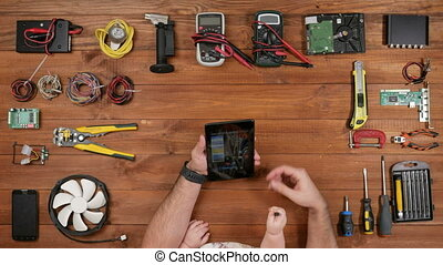 Male engineer with his son looking photo on tablet plate. Boy holding a screwdriver in his hand. Wooden table top view