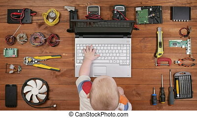 Kid sitting with his father for the workplace computer repair and press the keys on a laptop. Wooden table top view