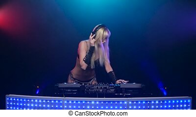 Erotic blonde DJ in sexy black lingerie twists vinyls....