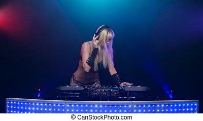 Erotic blonde DJ in sexy black lingerie twists vinyls....