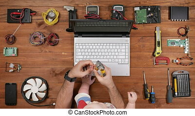 Kid sitting with his father as an engineer at the workplace. Man cuts off a piece of wire. Wooden table top view