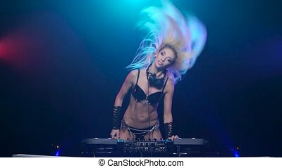 Dj woman blond dancing to the rhythm of playing music,...