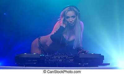 Sexy woman blonde DJ in leather lingerie playing on vinyl -...