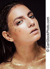 Close up portrait of beautiful woman with creative gold make up