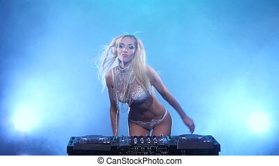 Blonde girl DJ sexy dances for mixing console. Smoky studio...