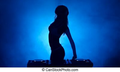 Silhouette of model woman DJ in the smoke mixes music
