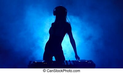 Silhouette of girl DJ in the smoke mixes music