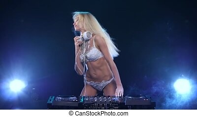DJ longhaired blonde woman twists vinyl and plays with hair