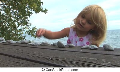 little blond girl counting pebbles