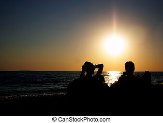 silhouettes of young couple on sunset sea background