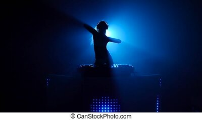 Blond girl dj sexy dancing in blue silhouette, dj table...