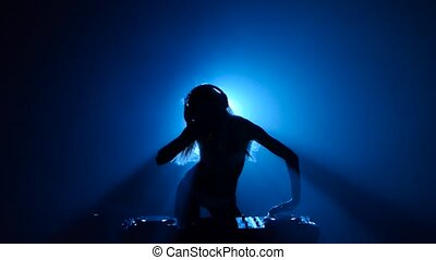 Model girl dj plays track and erotically dancing in silhouette