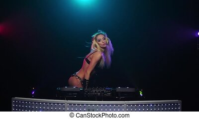 Blonde DJ girl sexy dancing for mixing console. Slow motion...