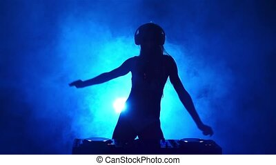 Silhouette of girl DJ in the smoke. Slow motion