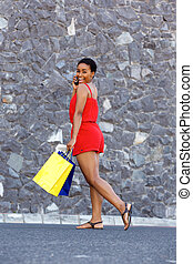 happy young black woman with shopping bags talking on cellphone
