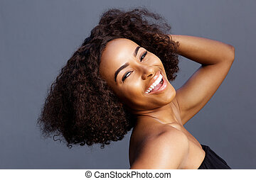 beautiful young black woman laughing with hand in hair