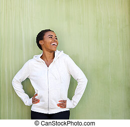 beautiful young black woman laughing against green wall