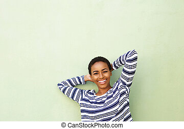smiling young woman with hands behind head