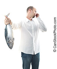 man with smelly fish - young man hold an smelly fish in his...